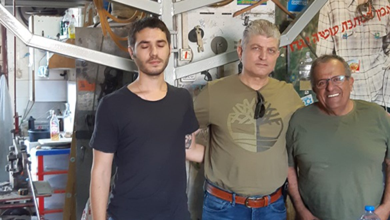 אמן המתכת איציק גמליאל, בועז קוקיא ודור קוקיא ליד חנוכיית ההנצחה צילום-ענת רסקין