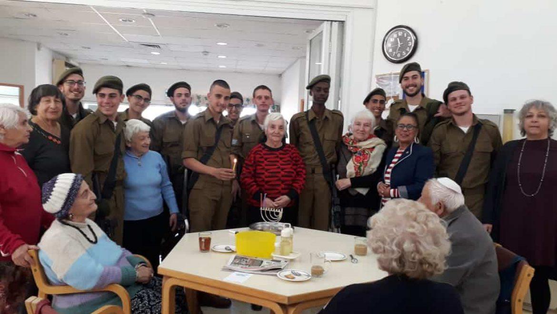 """חיילי בסיס הנח""""ל מדליקים נרות חנוכה עם המבוגרים מבית גלעד בערד צילום-אילנה פורת"""